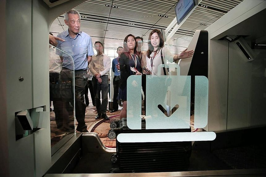 PM Lee at the automated bag drop, where passengers' photos are taken and matched against their passports for security.