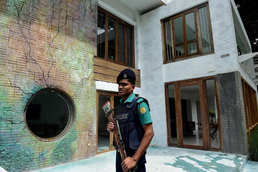 A Bangladeshi policeman standing guard at the old location of the Holey Artisan Bakery cafe a year after a deadly siege, in Dhaka on July 1, 2017.