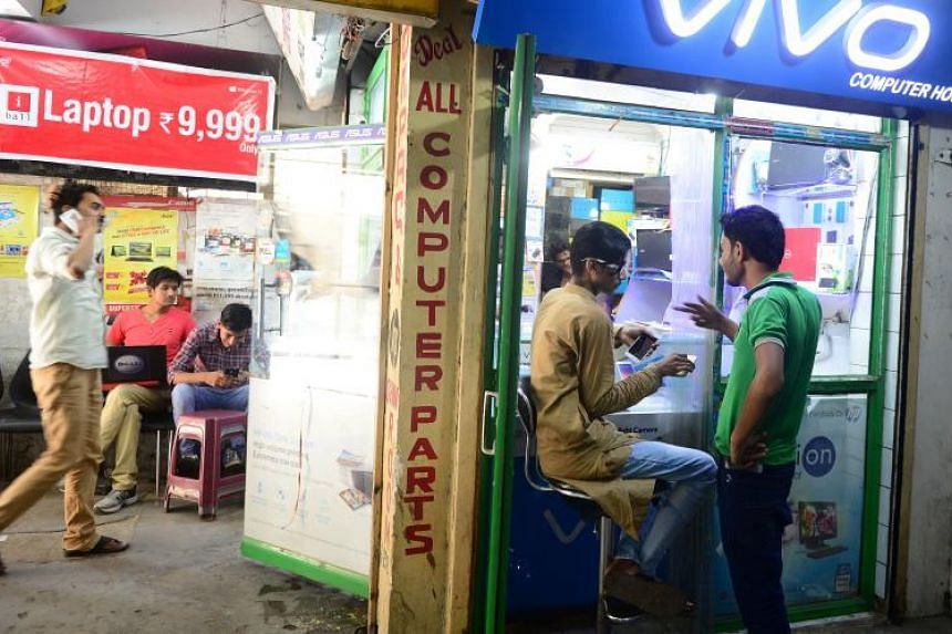 An Indian electronics vendor speaks with a customer at his outlet at Indira Bhawan in Allahabad.