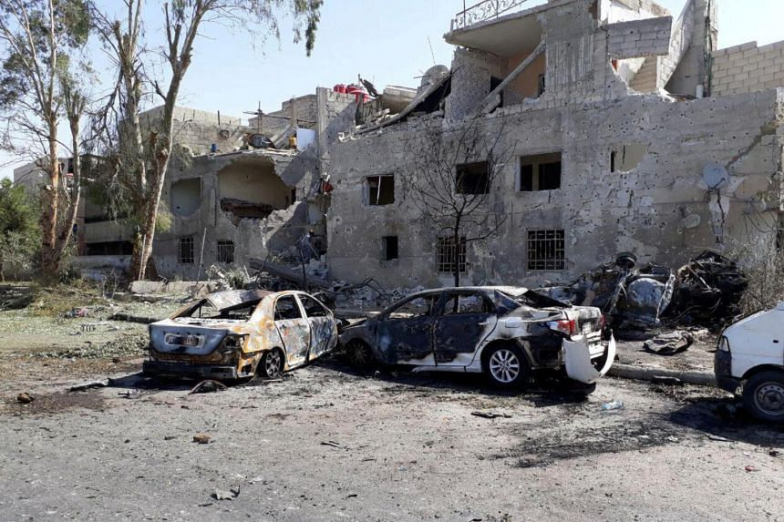 Damaged cars are seen at the site of a suicide bombing in Damascus on July 2, 2017.
