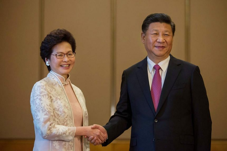 China President Xi Jinping shakes hands with Hong Kong's new Chief Executive Carrie Lam.