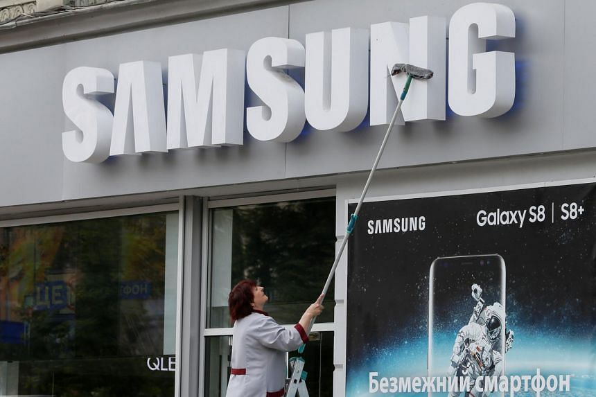 An employee cleans the corporate logo of South Korea's Samsung Electronics at its store in central Kiev