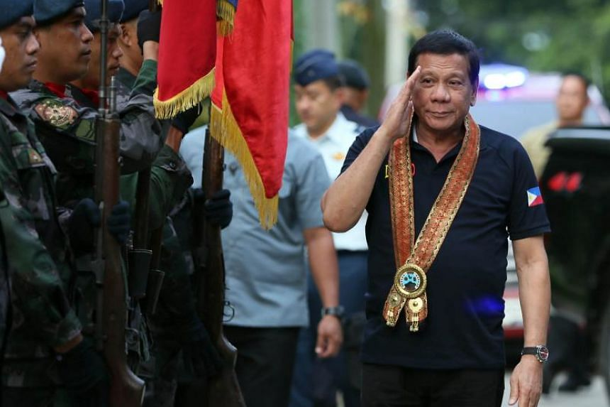 Philippine President Rodrigo Duterte (right) saluting during a visit at a police headquarters in Davao city.
