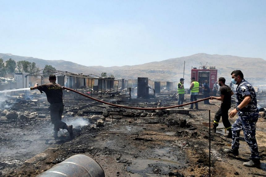 Firefighters putting out a fire at a camp for Syrian refugees near the town of Qab Elias, Lebanon, on July 2, 2017.