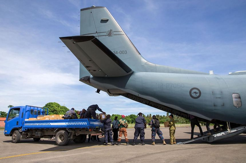 Australian Defence Force and Papua New Guinea Police Force personnel unloading ballot papers from a plane, in Papua New Guinea on June 15, 2017.