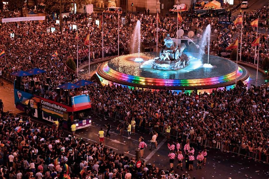People gather at Cibeles square to watch participants on floats.