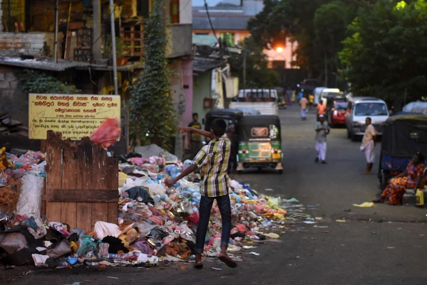 A Sri Lankan man throwing rubbish onto a pile of garbage on a street in Colombo on June 26, 2017.