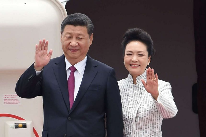 China's President Xi Jinping and his wife Peng Liyuan wave upon their arrival at Hong Kong's international airport.