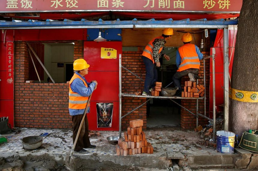 Workers building a brick wall across the front of a restaurant in a hutong alley in Beijing, China on May 5, 2017.