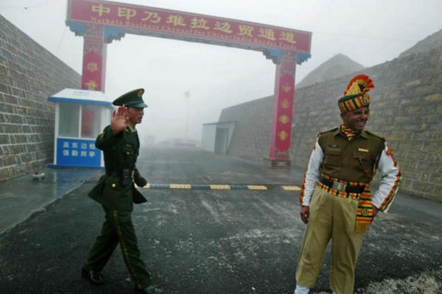 A Chinese soldier (left) and an Indian soldier standing guard at the Chinese side of the ancient Nathu La border crossing between India and China on July 10, 2008.