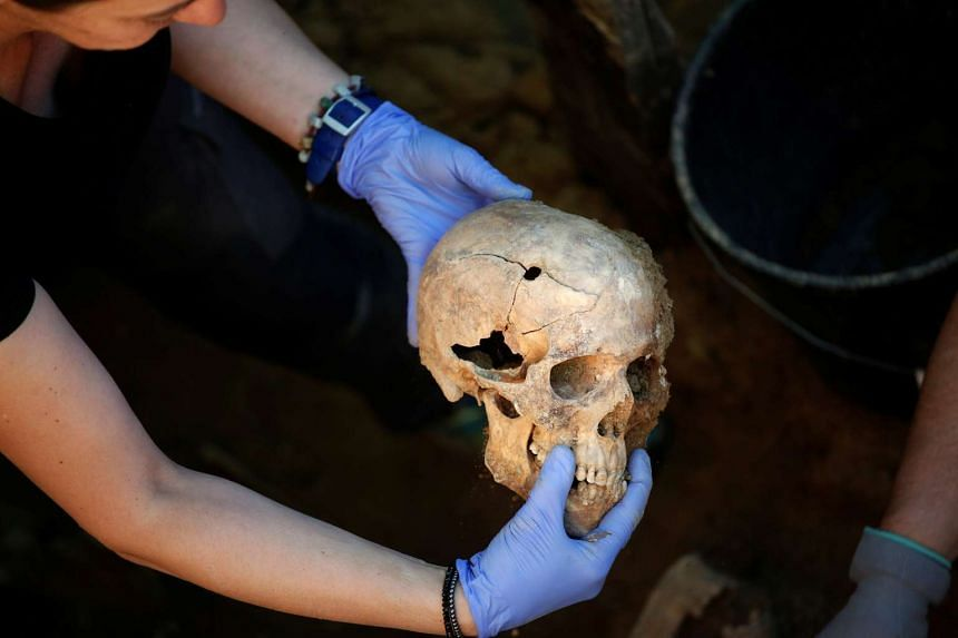 A member of the Association for the Recovery of Historical Memory holds a human skull with a bullet hole during the exhumation of a grave in which they believe may be the remains of Timoteo Mendieta, who was shot in 1939 by forces of dictator Francis