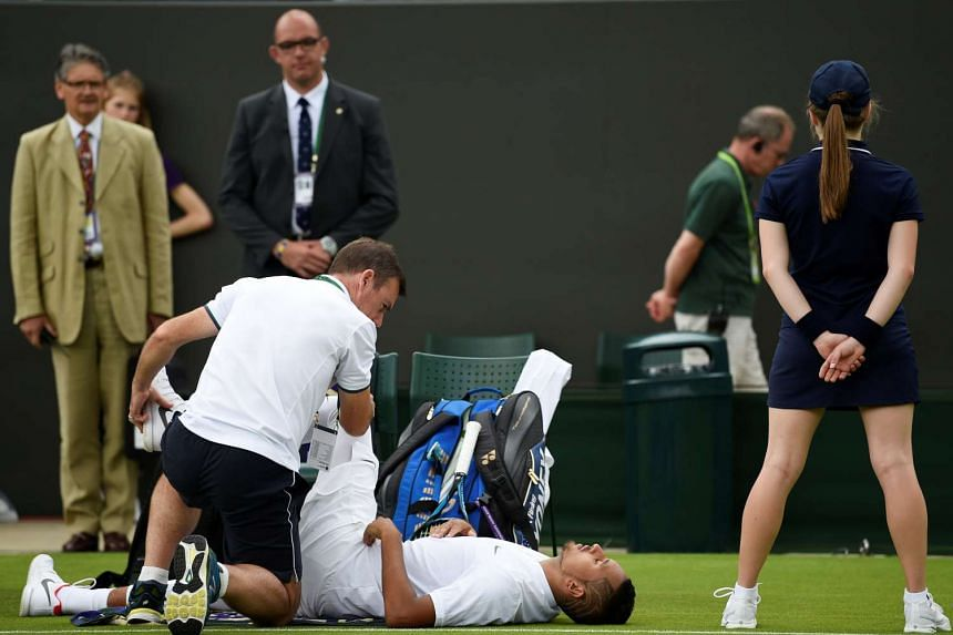 Australia's Nick Kyrgios in pain as he receives medical attention after an injury during his first-round match against France's Pierre-Hugues Herbert at Wimbledon on July 3, 2017.