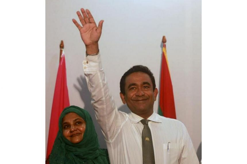 Newly elected Maldives President Abdulla Yameen raising his hand at his party's headquarters for election day, at Nasandura Palace Hotel in Male on Nov 16, 2013.