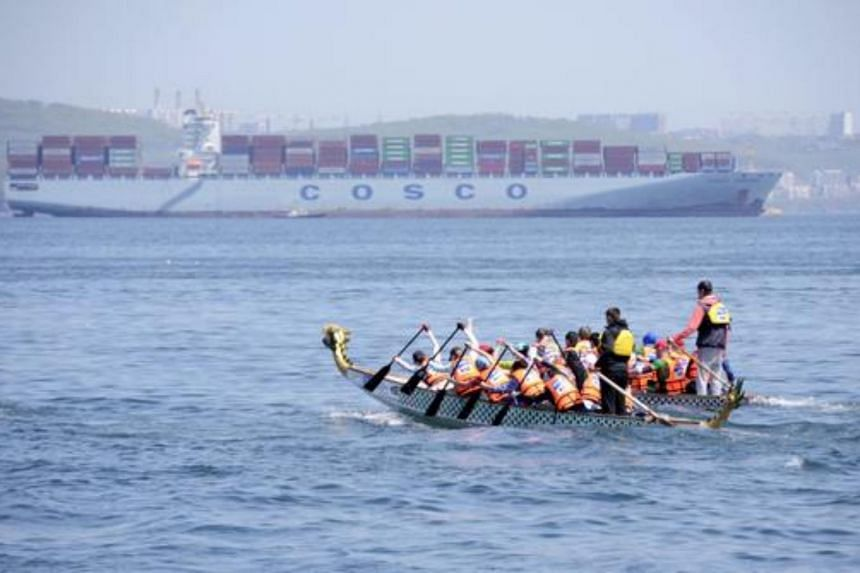 Athletes competing in a Dragon boat pulling race in the Sea of Japan waters, with the COSCO Yantian cargo ship seen in the background, near the far eastern port of Vladivostok, Russia,on May 23, 2015.