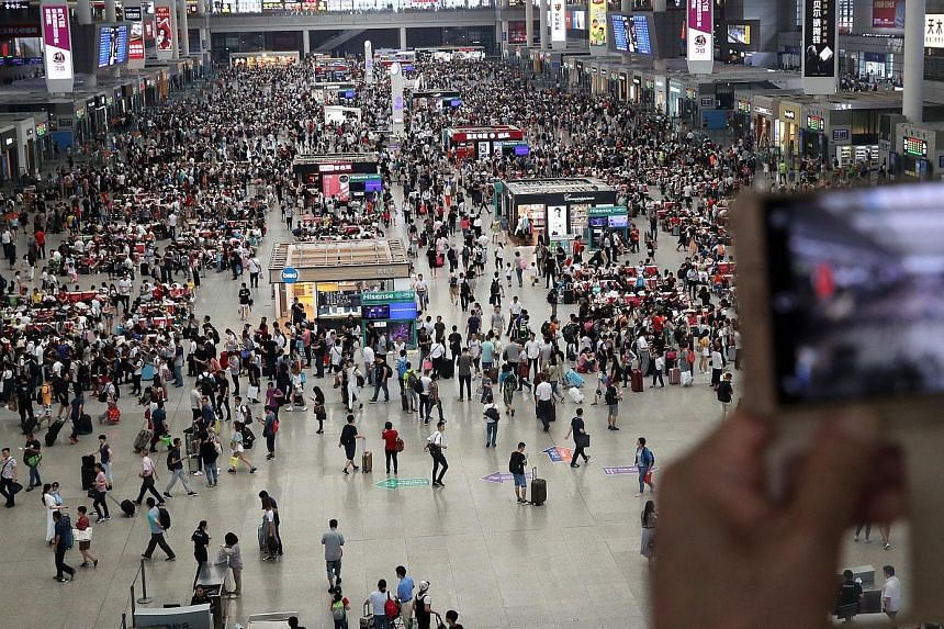 Travellers swarming across the Shanghai Hongqiao Railway Station last Saturday - the first day of shu yun, or China's summer transport peak period. In all, 598 million passenger trips are expected to be made by train over the period, which ends on Au