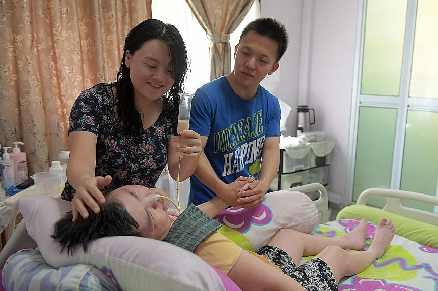 "Ms Grace Koh feeding milk to her bedridden mother with the help of her brother Joshua Koh. The siblings, who both have full-time jobs, also look after their father who needs intensive care after a fall left him with a brain injury. ""At the end of a l"