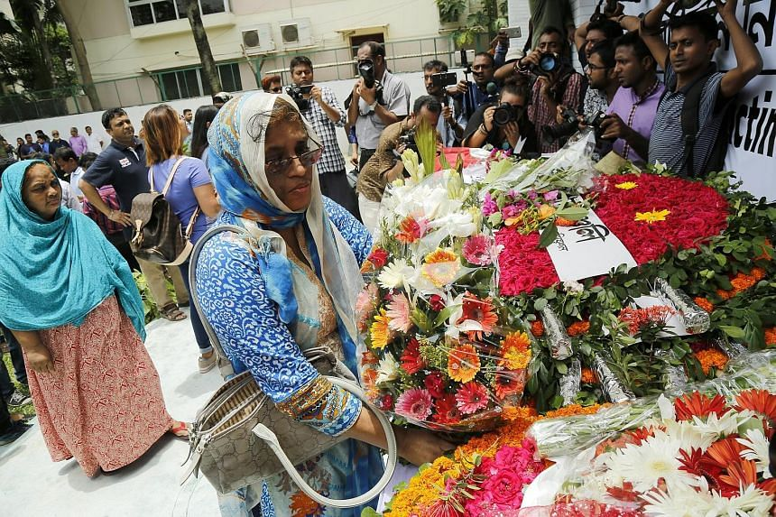 People paying their respects at the new building where the Holey cafe used to be in Dhaka, Bangladesh, on Saturday. Last year's terrorist attack by members of local militant group Jamayetul Mujahideen Bangladesh killed more than 20 people.