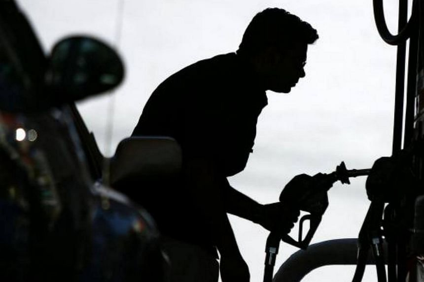 A resident looking at the price of gasoline as he fuels up his car at a gas station in South Beach, Florida.