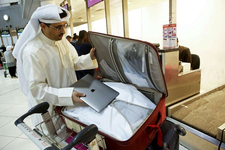 Kuwaiti social media activist Thamer al-Dakheel Bourashed putting his laptop inside his suitcase at Kuwait International Airport in Kuwait City before boarding a flight to the United States on March 23, 2017.
