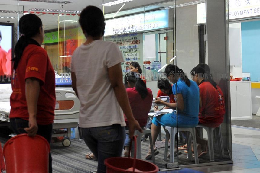 Maids seen seated inside a maid agency at Bukit Timah Shopping Centre.