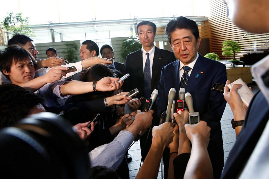 Japan's Prime Minister Shinzo Abe speaking to reporters as he arrives at his office, on July 3, 2017.