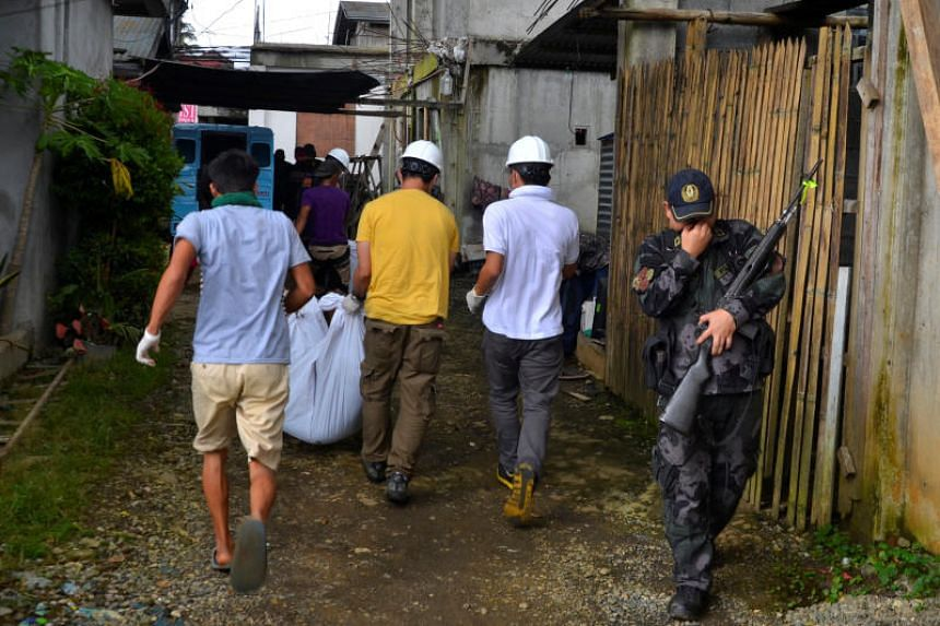 A group of rescue volunteers carry a body they found at the beginning of the fight between government troops and Maute group militants in Maraw in the Philippines.