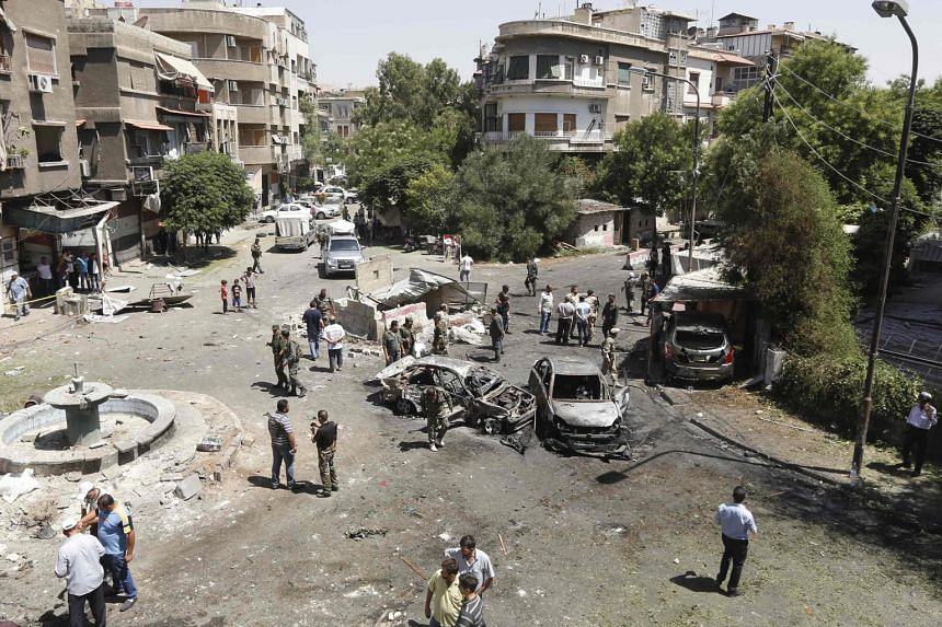 The scene of a suicide car bomb attack in Damascus' Tahrir Square district yesterday. Two other cars intercepted by security forces were blown up on the city's outskirts.