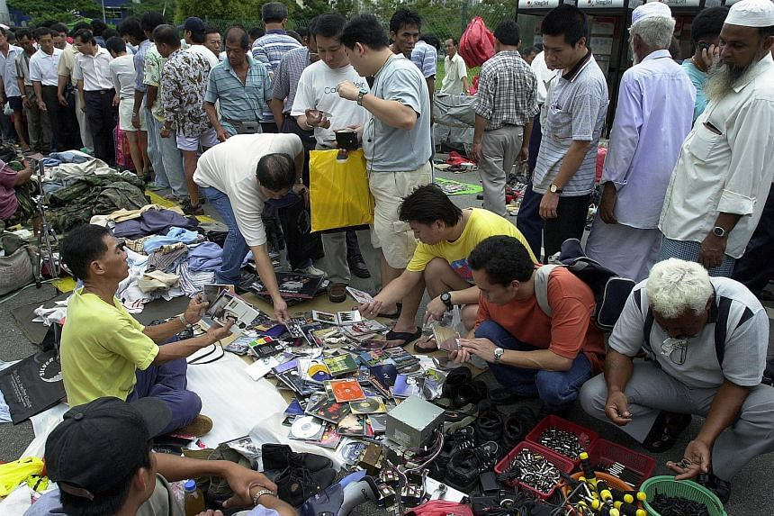 Customers browsing the goods on sale at Sungei Road flea market.