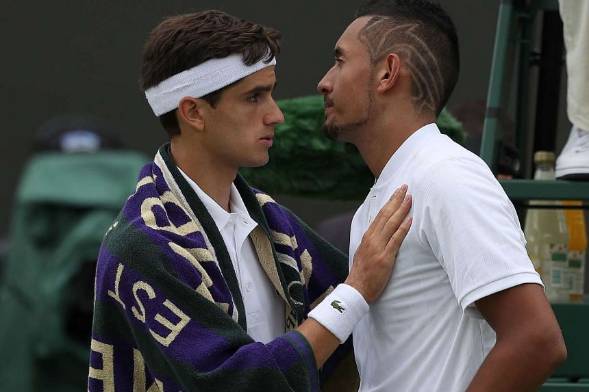 Nick Kyrgios is consoled by France's Pierre-Hugues Herbert after retiring from their match on the first day of the Wimbledon Championships in London.