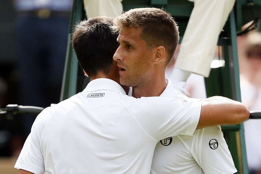Klizan (right) at the net with Djokovic after retiring from their first round match.