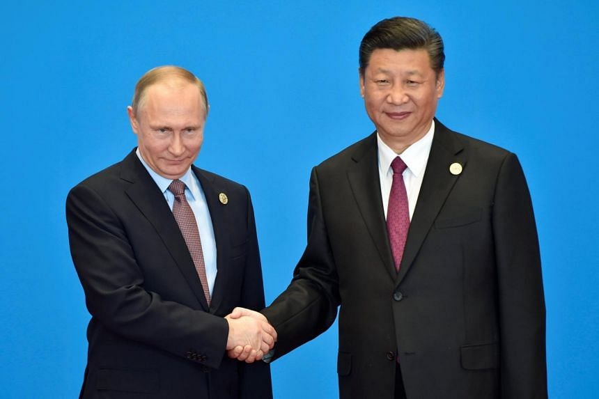 Russian President Vladimir Putin (left) shaking hands with Chinese President Xi Jinping during the welcome ceremony for the Belt and Road Forum, at the International Conference Center in Yanqi Lake, north of Beijing, on May 15, 2017.