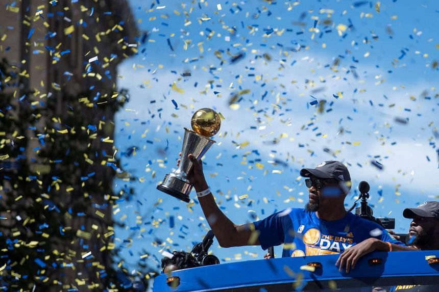 Golden State Warriors forward Kevin Durant hoisting the MVP trophy during the team's NBA championship victory parade in downtown Oakland, California on June 15, 2017.