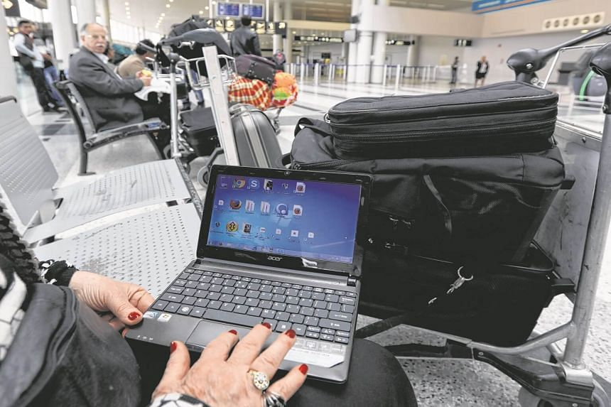 A Syrian woman travelling to the United States through Amman opens her laptop before checking in at Beirut international airport.