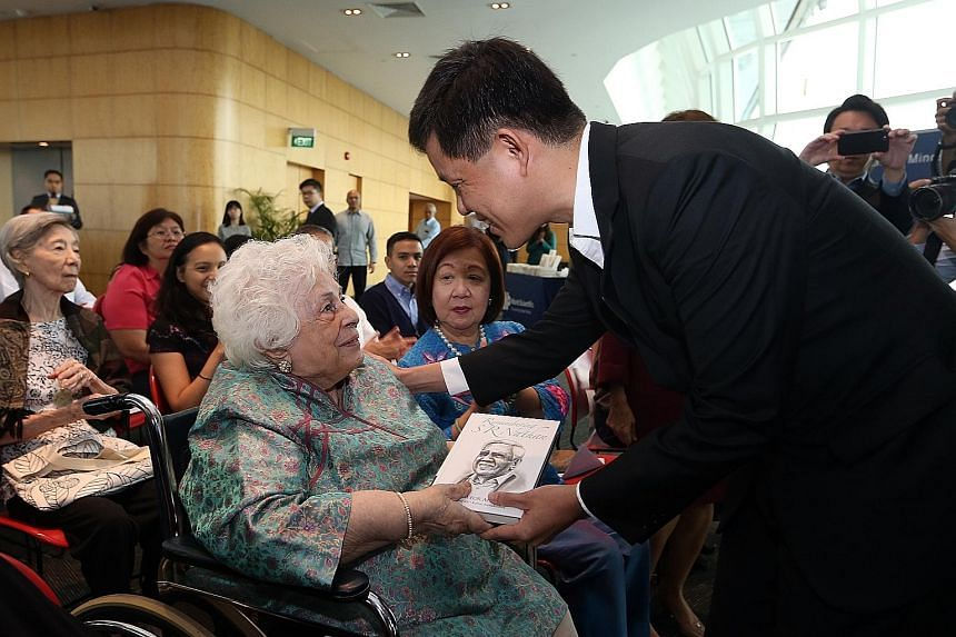 Mr Chan Chun Sing, Minister in the Prime Minister's Office, presenting a copy of Remembering S R Nathan: A Mentor For All Seasons to Mrs Nathan at the launch of the book at the National Library Building yesterday.