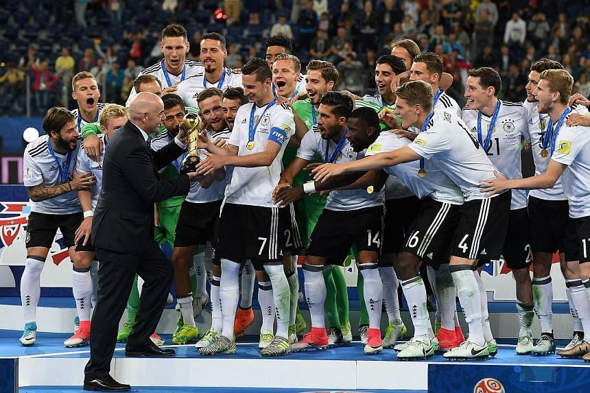 Left: Germany's stand-in captain Julian Draxler receiving the Confederations Cup trophy from Fifa president Gianni InfantinoBelow: Germany forward Lars Stindl slotting home into an empty net for the winner against Chile.Bottom: Forward Timo Werner of