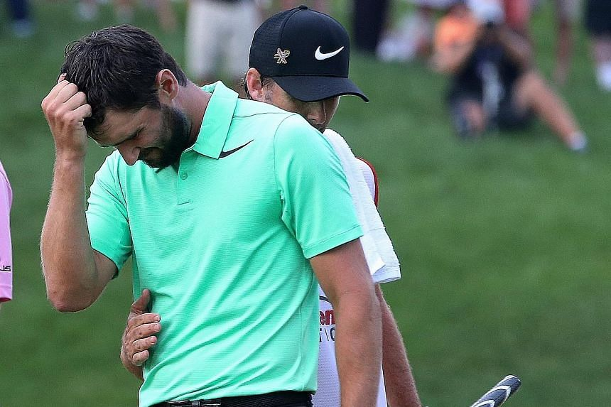 Kyle Stanley of the United States finding it hard to control his emotions while being congratulated by his caddie Bryan Reed after making a par putt on the first play-off hole to win the PGA National on Sunday.