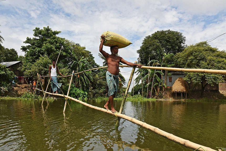 Villagers using a makeshift bamboo bridge to cross flooded areas in India's north-eastern state of Assam on Sunday. Weather officials say several rivers are maintaining a rising trend, and many of them have breached their banks.