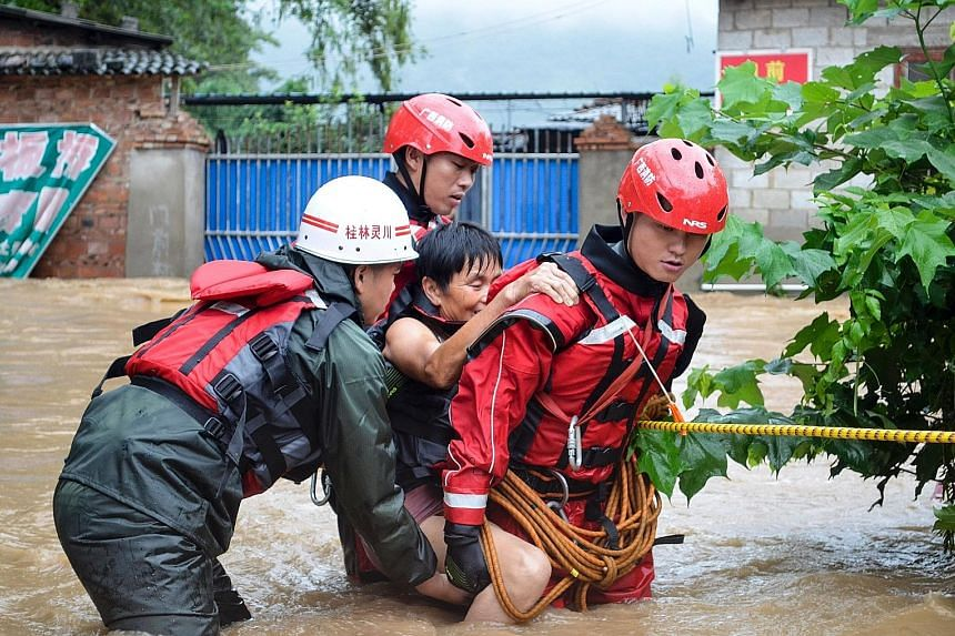 Rescue workers helping an elderly woman cross a flooded street in Guilin, Guangxi province. In Changsha (main picture), Hunan province's capital, days of torrential rain have caused the Xiangjiang river to exceed its record flood level.