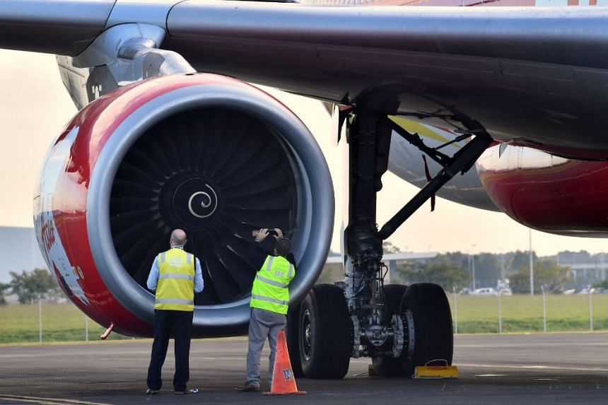 Officials inspect an engine of Malaysian budget carrier AirAsia X Flight D7207. The flight was diverted and forced to land because an engine was damaged during take-off by what was thought to be a bird strike at Brisbane Airport.