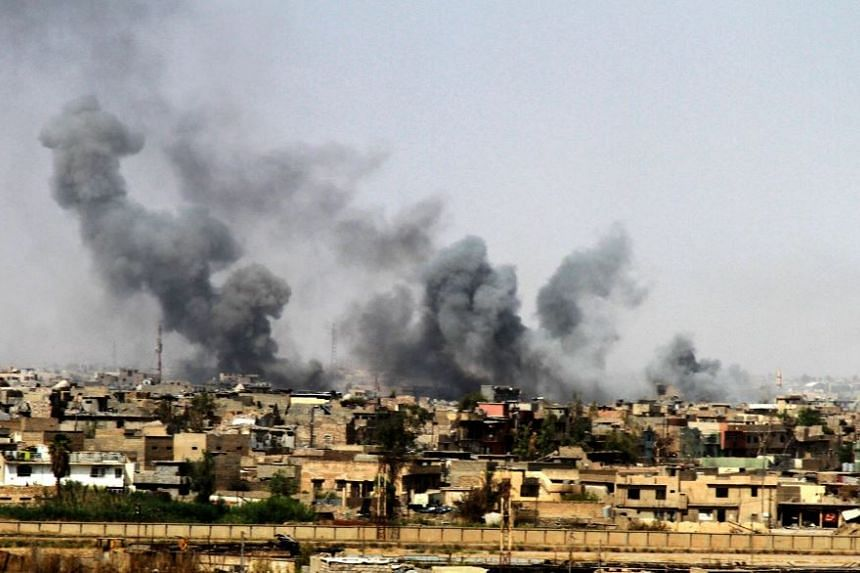 A general view showing smoke clouds rising from the western part of Mosul city, Iraq.