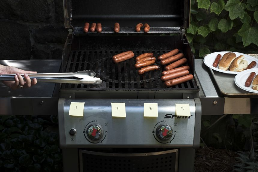 Hot dogs on the gas grill, cooked until well browned.