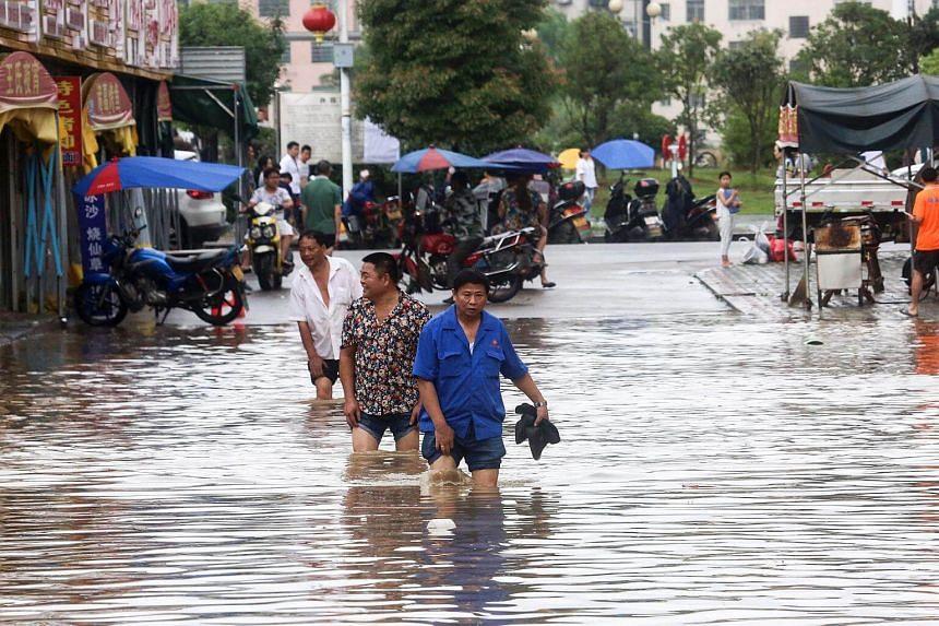 People walking along a flooded street in Loudi, Hunan province, on July 2, 2017.