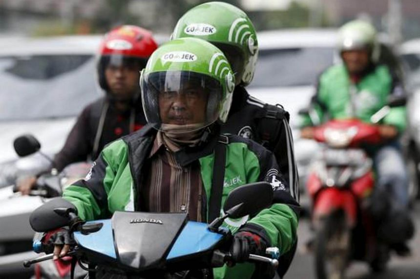 A driver and passenger ride on a motorbike, part of the Go-Jek ride-hailing service.