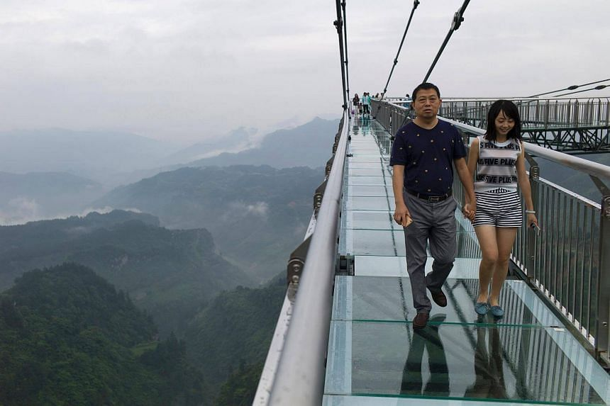 A couple walks on a glass-bottomed skywalk, certified as the world's longest, at the Ordovician park in Wansheng on June 1, 2017.