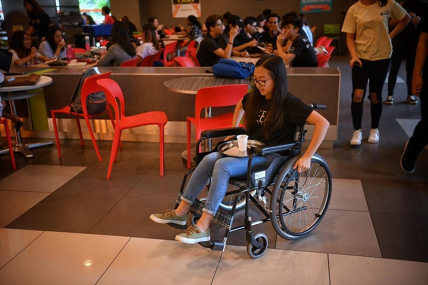 Business student Celine Lee balances a tray of water as she tries navigating around in a wheelchair during a campaign to encourage a more inclusive and respectful campus, and better integrate students with special educational needs and disabilities.