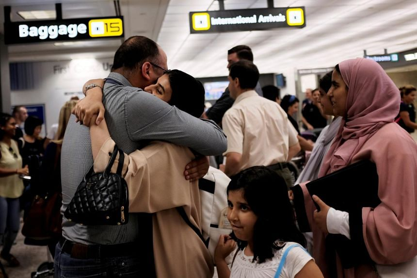 A family embracing each other as members arrive at Washington Dulles International Airport.