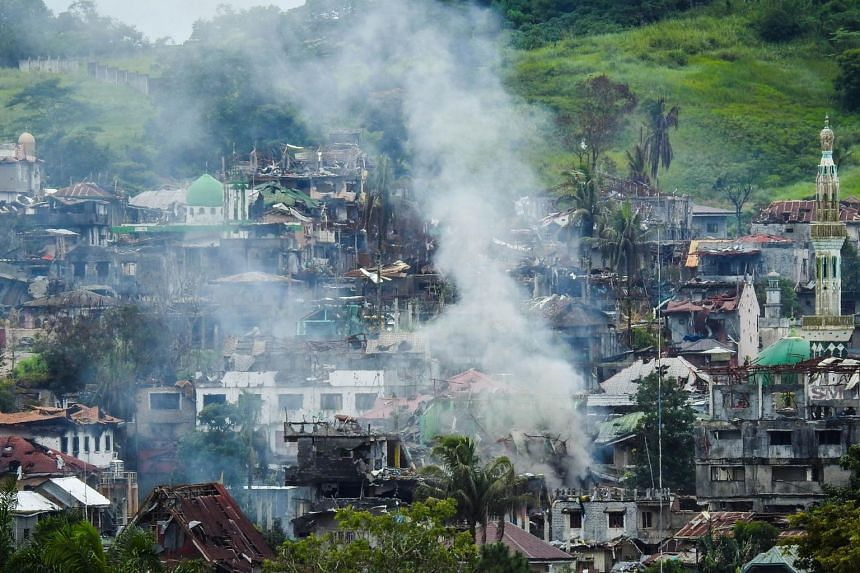 Smoke billows from burning houses as fighting between government troops and Islamist militants continues in Marawi on the southern island of Mindanao on July 3, 2017.
