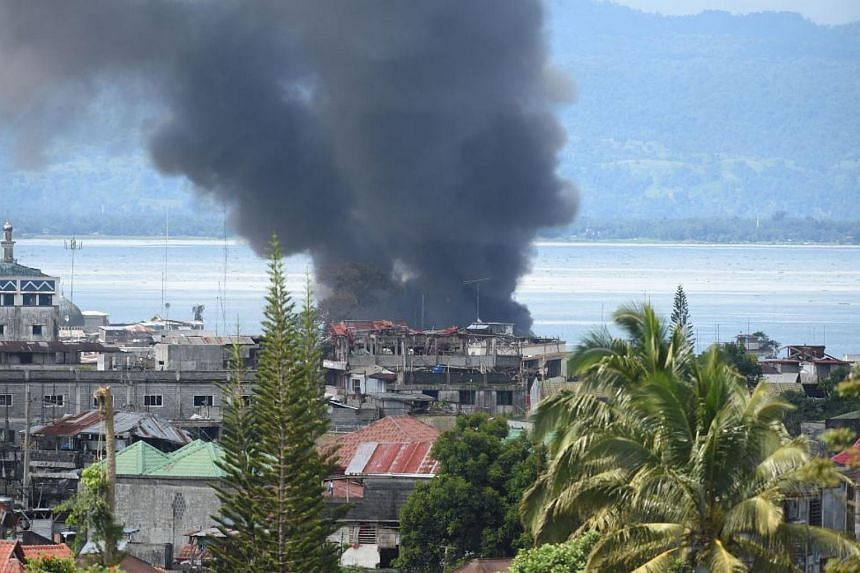 Black smoke billows from burning houses after an aerial bombing on militant Islamist positions in Marawi, on June 27, 2017.