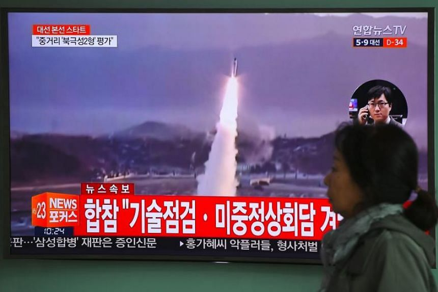 A woman walks past a television screen showing file footage of a North Korean missile launch, at a railway station in Seoul on April 5, 2017.