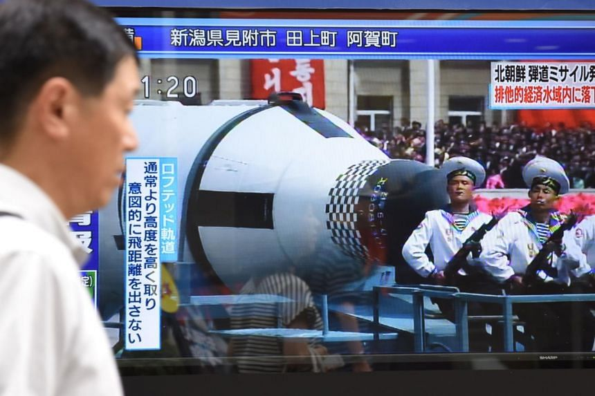 A pedestrian walks past a screen in Tokyo on July 4, 2017 broadcasting file news footage of a military parade showing North Korean soldiers and a missile.